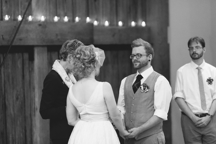 Stylish groom looking at bride while holding hands during wedding cermeony.
