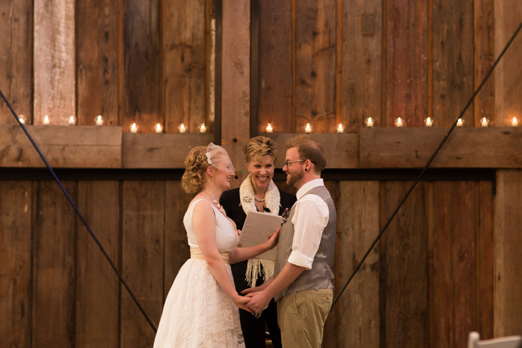Bride and groom and officiant during barn wedding ceremony.
