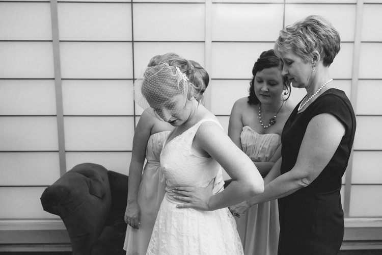 Mother of the bride and maid of honor lacing up bridal gown.