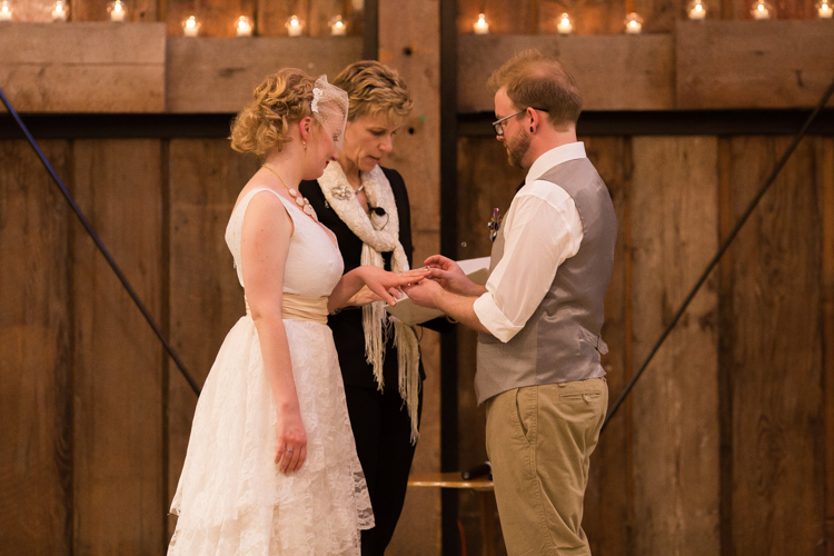 Groom puts ring on bride's finger.