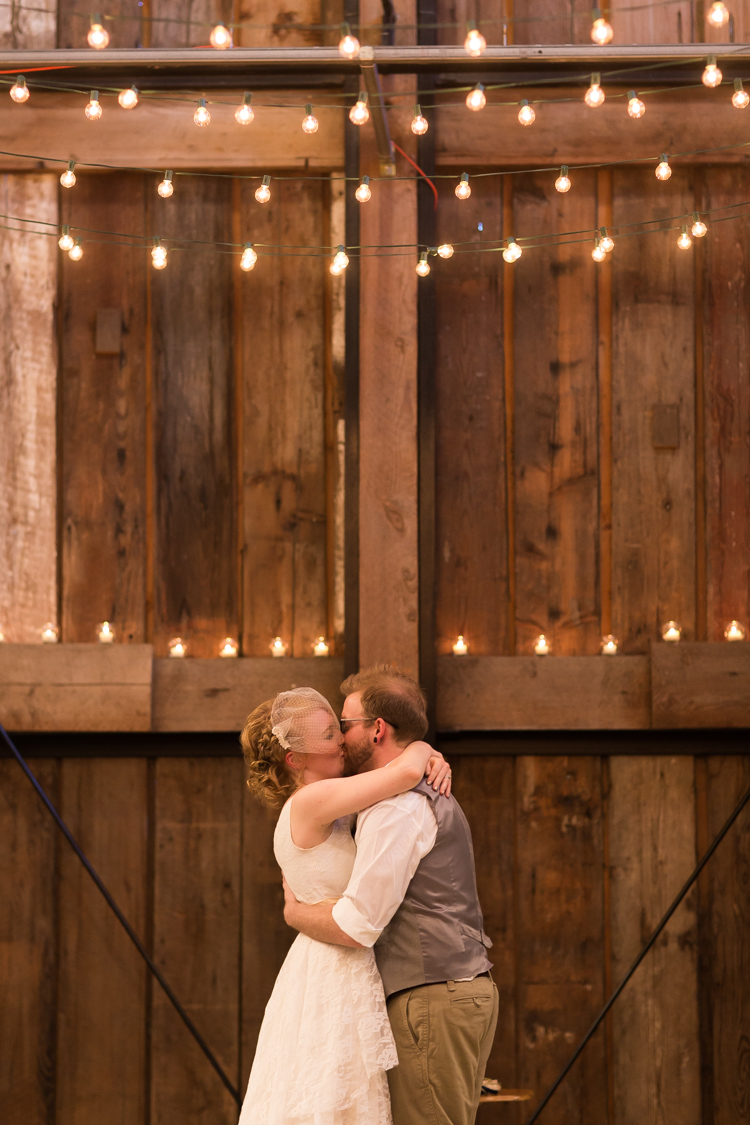 First kiss at wedding ceremony in pickering barn.