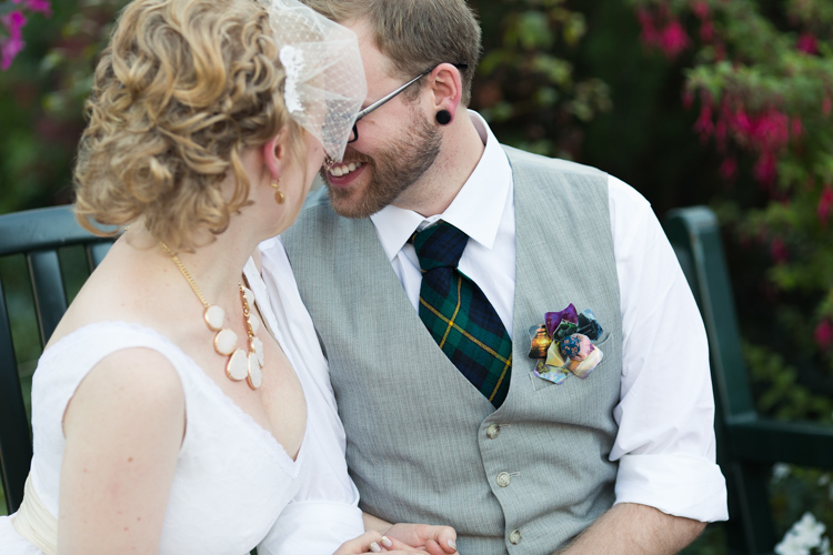Bride and groom nuzzle after wedding ceremony. Groom wears vest with green plaid tie and diy magic the gathering boutonniere and bride wears birdcage veil and chunky necklace.
