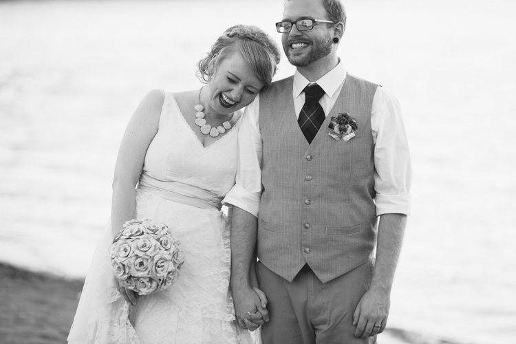 Black and white photo of bride and groom laughing during after ceremony wedding formals.