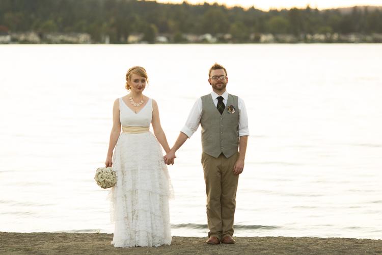 Stylish bride and groom hold hands at lake sammamish.
