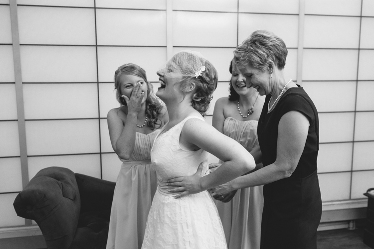 Bride and bridesmaids laughing before wedding.