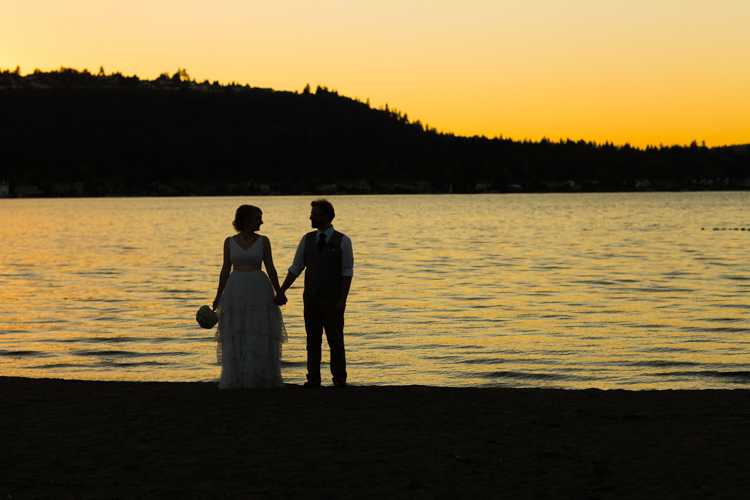 Bride and groom hold hands during sunset over lake sammamish in washington.