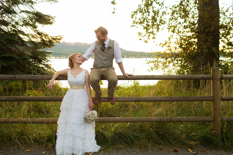 rustic photo with bride and groom sitting on fence near lake sammamish. .