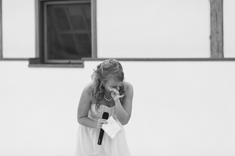 Sister of the bride and maid of honor cry during wedding toasts.