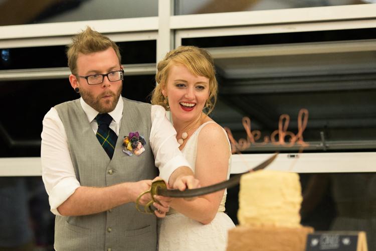 Bride and groom cut wedding cake with sabre sword.