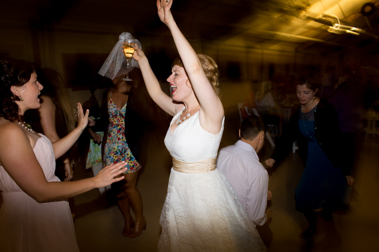 Bride dancing holding glass of champagne at wedding reception