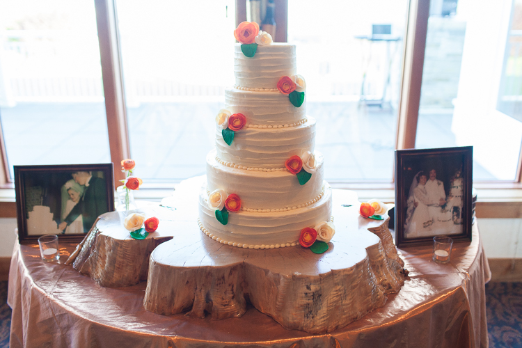 white 5 tier cake on wood slab