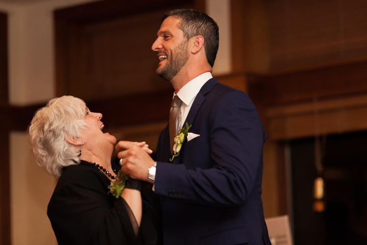 groom laughing dancing with mother