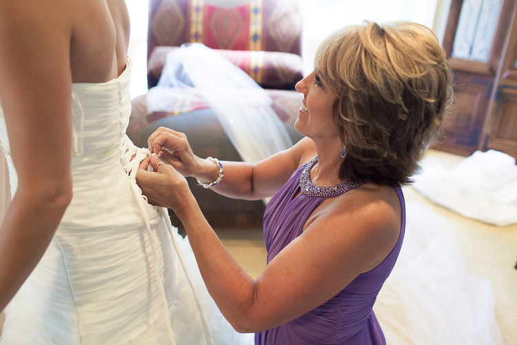 mom buttoning up bride's gown