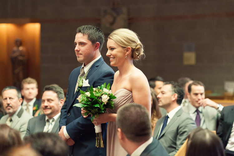 bridesmaid and groomsman walking down aisle at catholic ceremony