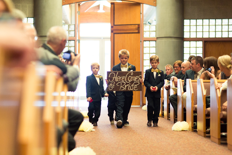 ring bearers holding here comes the bride sign