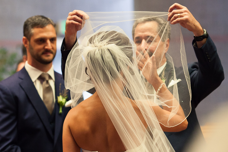 dad removing veil from bride