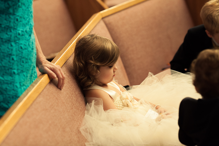 flower girl sitting at wedding ceremony