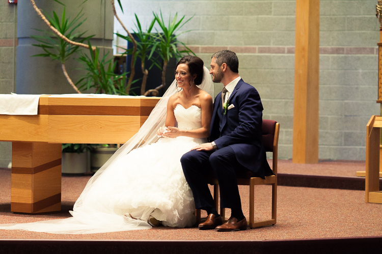 bride and groom sitting together at alter of catholic church