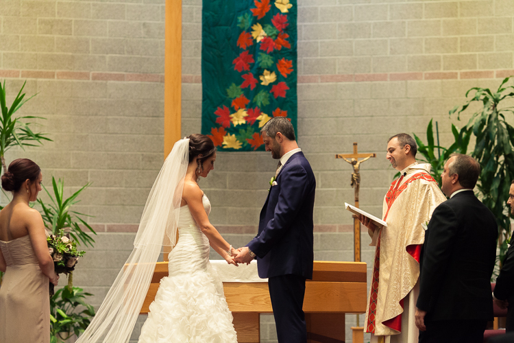 bride and groom holding hands at alter of catholic church