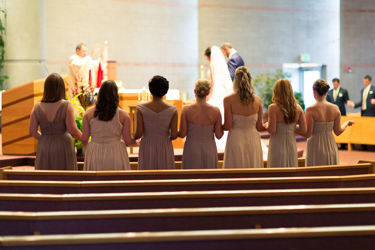 bridesmaids standing in front aisle of catholic wedding ceremony