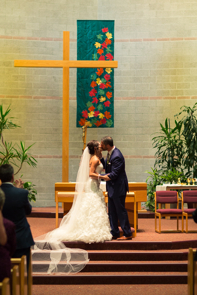 bride and groom kissing at catholic wedding ceremony