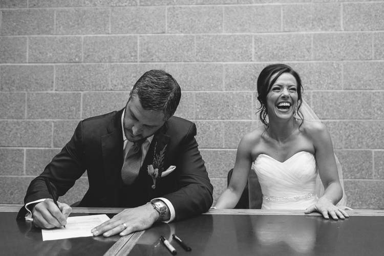bride laughing while signing the marriage license