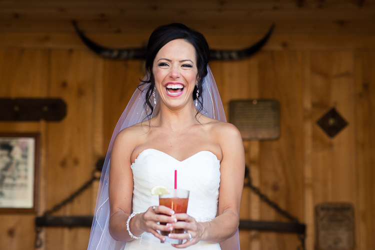 bride laughing wearing horns holding a drink