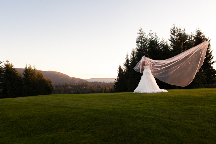 bride standing on a hill with veil blowing in the wind in snoqualmie