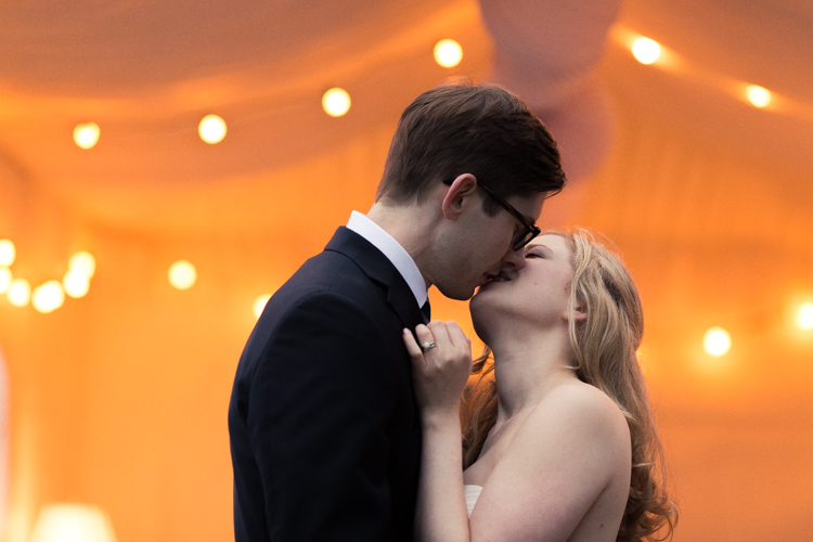 romantic kiss under the twinkling lights at destination wedding.
