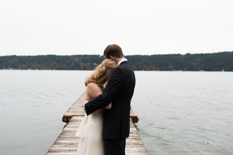 Beautiful couple hugs on dock before their wedding ceremony.