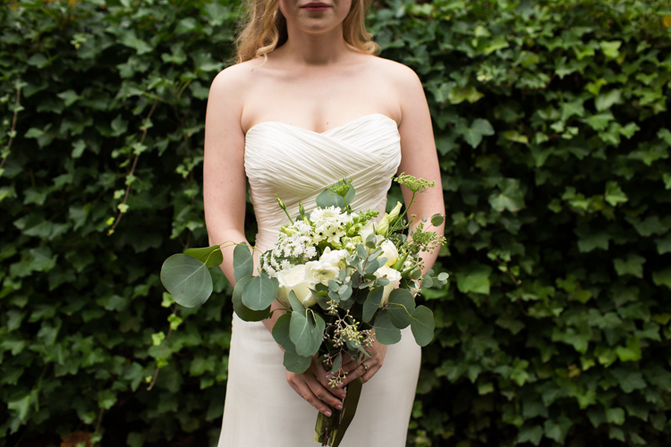 Seattle bride holds a white and green bouquet in front of her ivory dress.