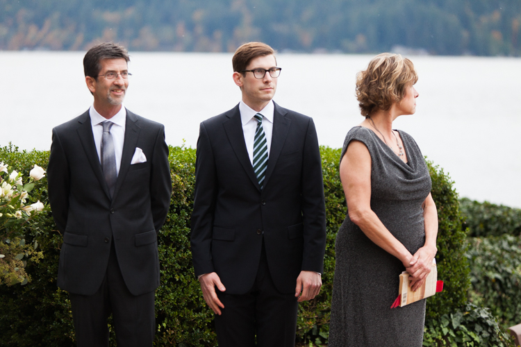 Groom and family wait for bride at intimate wedding ceremony.