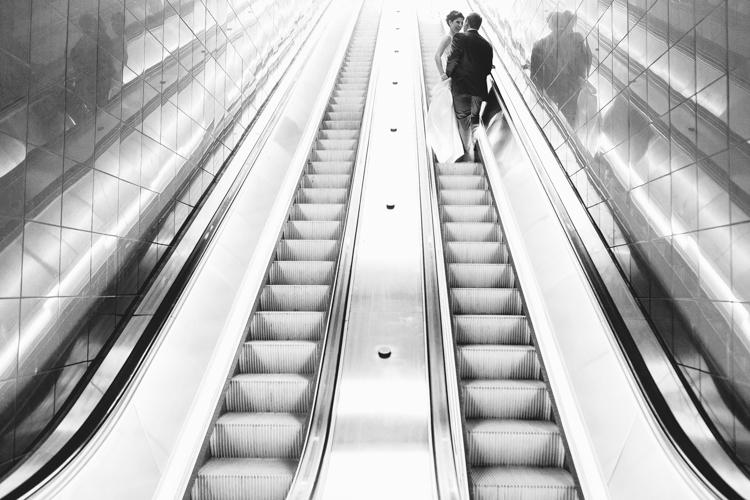 bride and groom on escalator